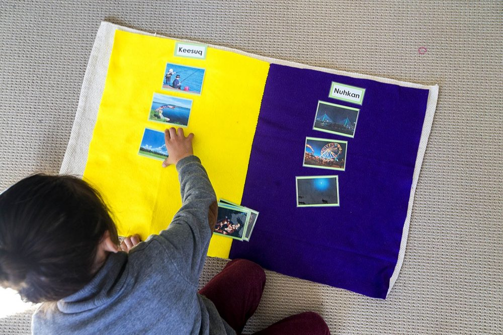 A student groups photos of day and night and matches them with the corresponding Wampanoag word on the floor. (Jesse Coista/WBUR)