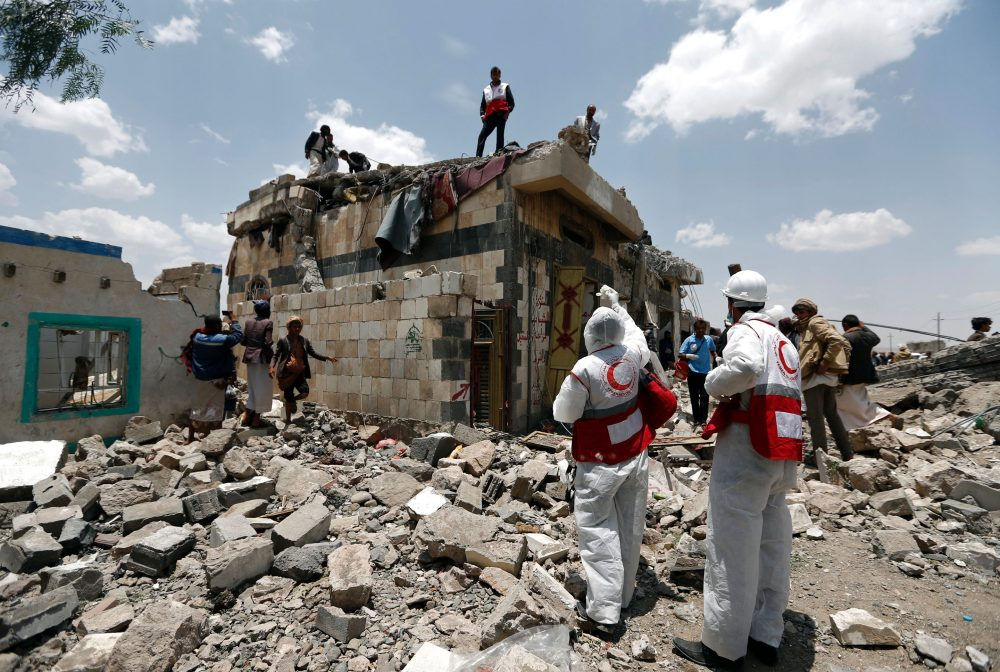 Yemeni Red Crescent workers and civilians stand at the site of an air raid in the Arhab area, around 13 miles north of Sanaa, on Aug. 23, 2017, where a Saudi-lead coalition has been bombing Iran-backed Huthi rebels. (Mohammed Huwais/AFP/Getty Images)