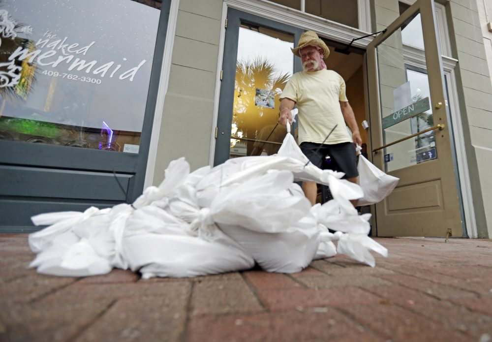 Lynn Dixon places sandbags outside his home decor store in Galveston, Texas, as Hurricane Harvey intensifies in the Gulf of Mexico Friday, Aug. 25, 2017. (David J. Phillip/AP)