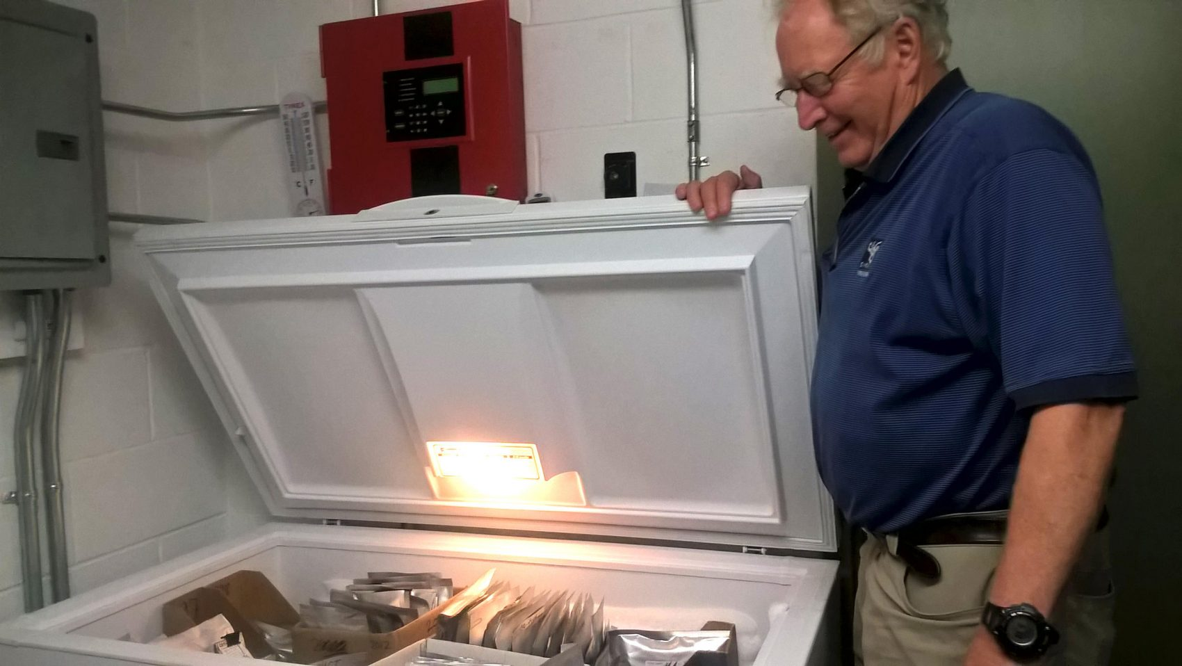 """New England Wildflower Society's Bill Brumback, opening the freezer that acts as the """"seed vault,"""" in Framingham, Mass. (Jill Kaufman/NEPR)"""