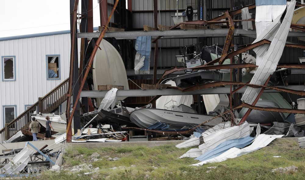 Two men check out damage to a boat storage facility caused by the effects of Hurricane Harvey on Sunday in Rockport, Texas. (Eric Gay/AP)