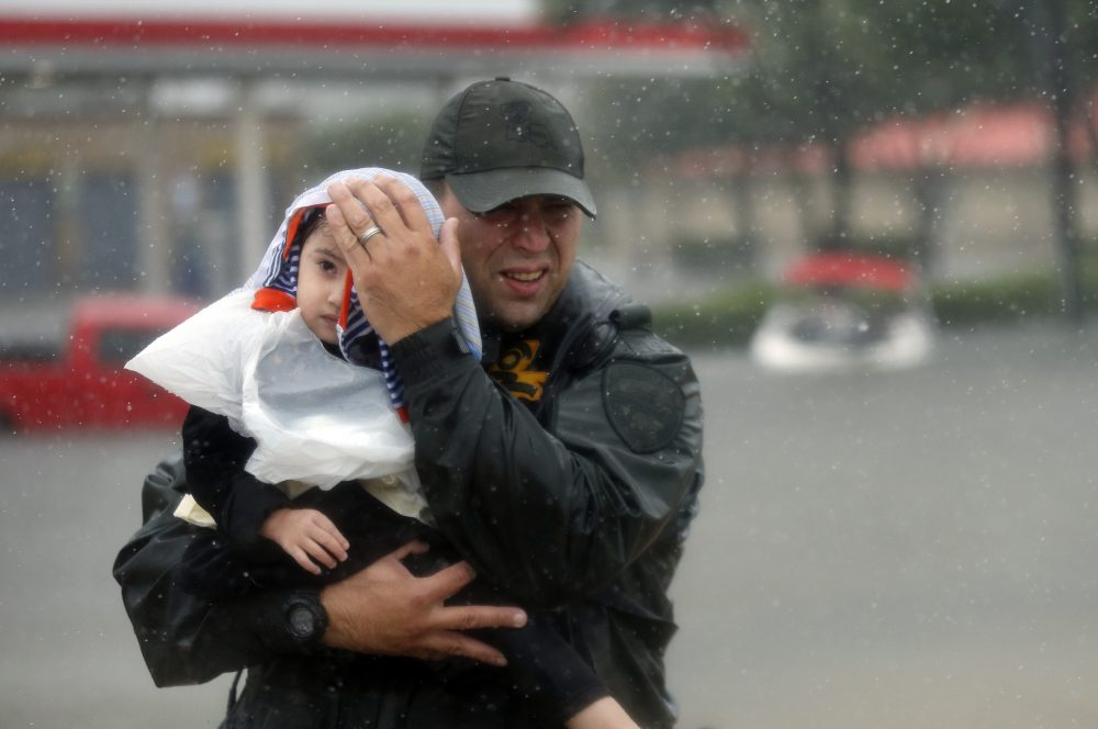 Sgt. Chad Watts, of the Louisiana Department of Wildlife and Fisheries, holds Madelyn Nguyen, 2, after he rescued her and her family by boat from floodwaters of Harvey in Houston on Monday. (Gerald Herbert/AP)