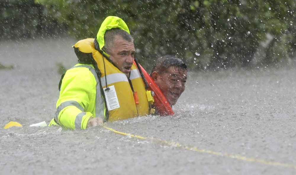 Wilford Martinez, right, is rescued from his flooded car by Harris County Sheriff's Department Richard Wagner along Interstate 610. (David J. Phillip/AP)