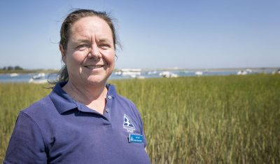 Mass Audubon's Liz Duff stands in the salt marsh off Conomo Point Road in Essex. (Robin Lubbock/WBUR)