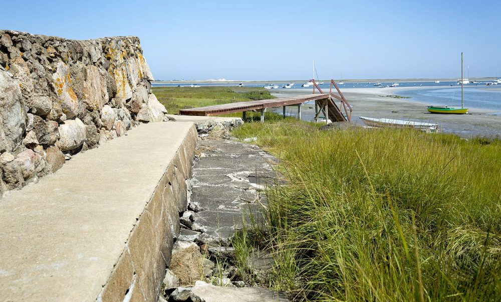 Walls constructed to protect buildings on the shore prevent the marsh's retreat as the ocean advances. Here only a small strip of marsh survives in front of a sea wall. (Robin Lubbock/WBUR)