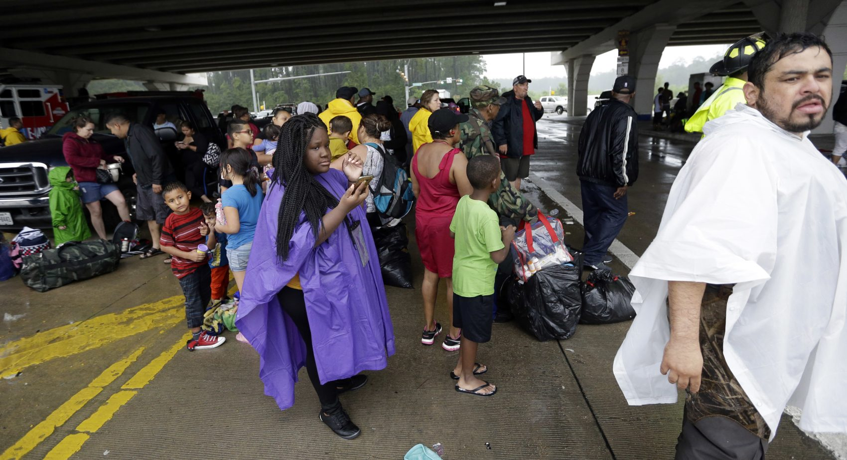Evacuees waits to be bused to safety after being evacuated from their homes as floodwaters from Tropical Storm Harvey rise Monday in Houston. (David J. Phillip/AP)