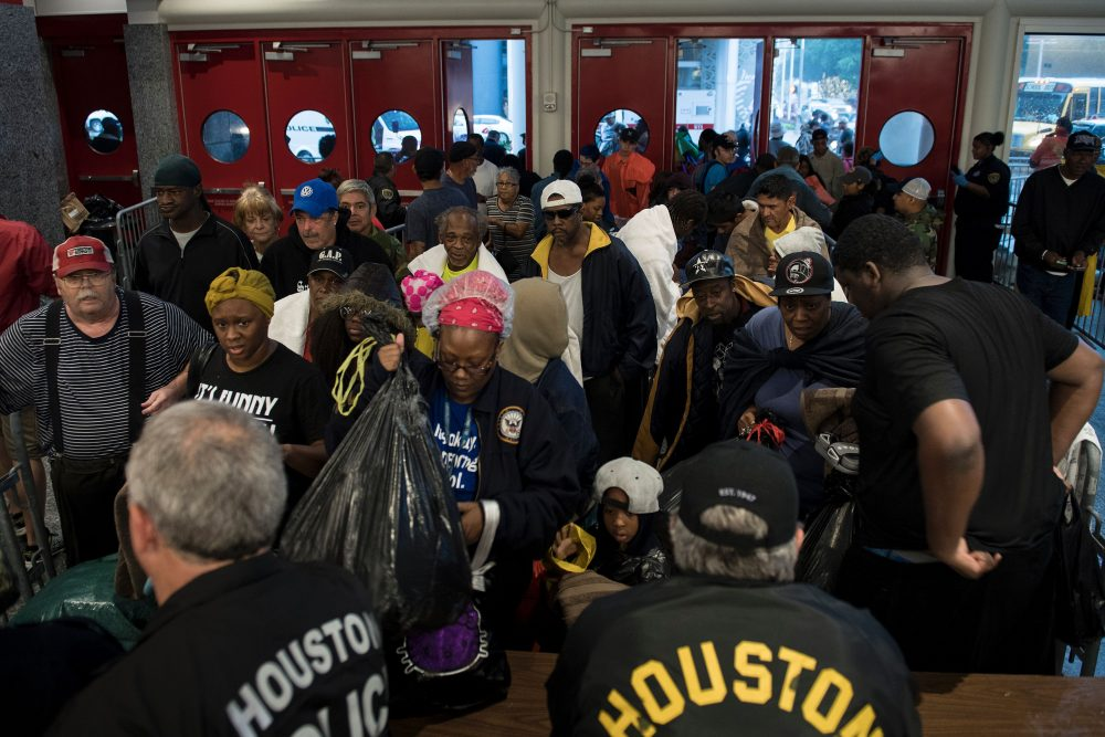 People wait to be checked by police before entering a shelter in the George R. Brown Convention Center during the aftermath of Hurricane Harvey on Aug. 28, 2017 in Houston, Texas. (Brendan Smialowski/AFP/Getty Images)