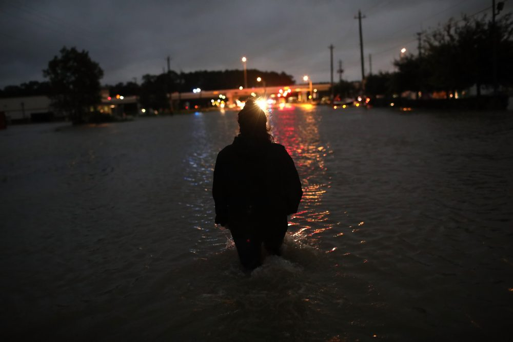 A Houston resident walks through waist deep water while evacuating her home after severe flooding following Hurricane Harvey in north Houston, Aug. 29, 2017. (Win McNamee/Getty Images)