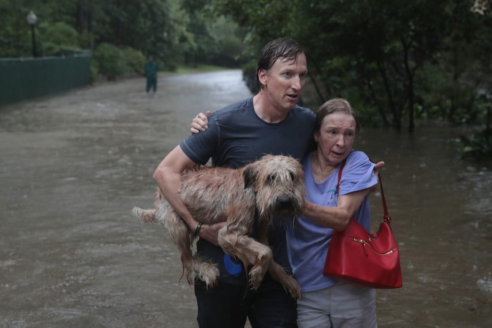 Andrew White (left) helps a neighbor down a street after rescuing her from her home in his boat in the upscale River Oaks neighborhood after it was inundated with flooding from Hurricane Harvey on Aug. 27, 2017 in Houston, Texas. (Scott Olson/Getty Images)