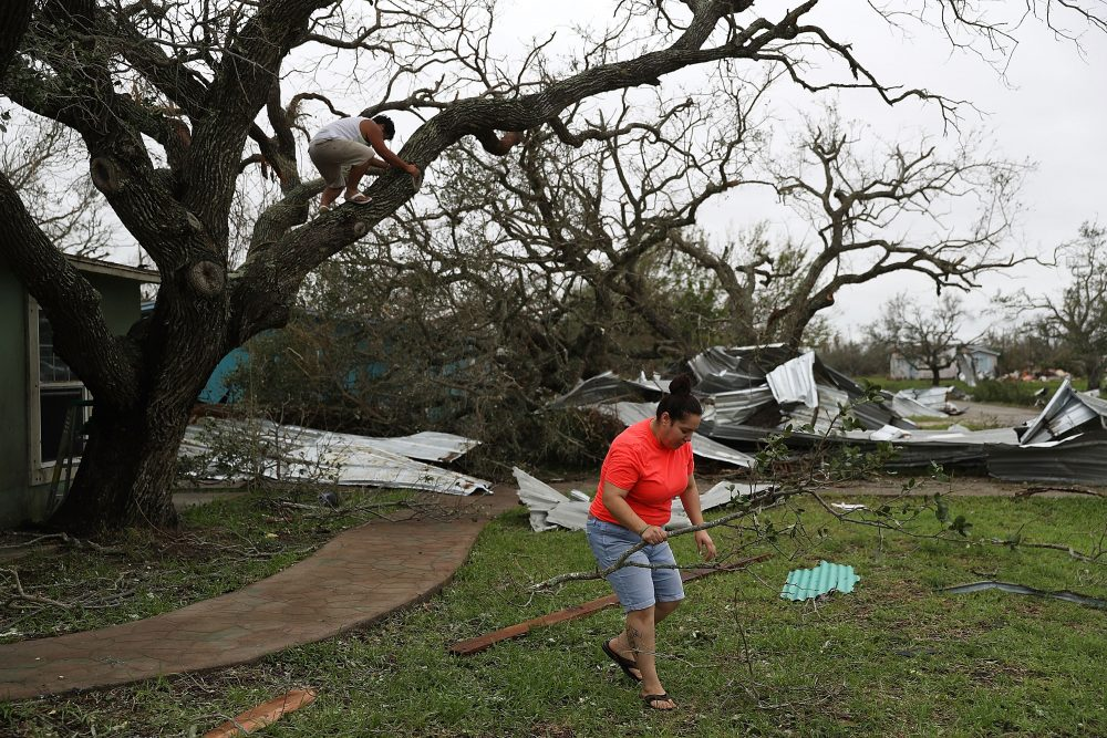 Joshua Nguyen (left) and Deserae Garcia clean up around their home after Hurricane Harvey passed through on Aug. 27, 2017 in Rockport, Texas. (Joe Raedle/Getty Images)