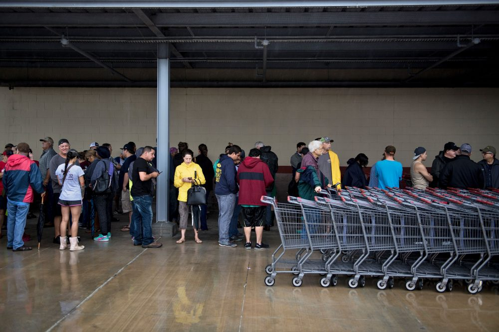 People wait in line for an H-E-B grocery store to open during the aftermath of Hurricane Harvey on Aug. 29, 2017 in Deer Park, Texas. (Brendan Smialowski/AFP/Getty Images)
