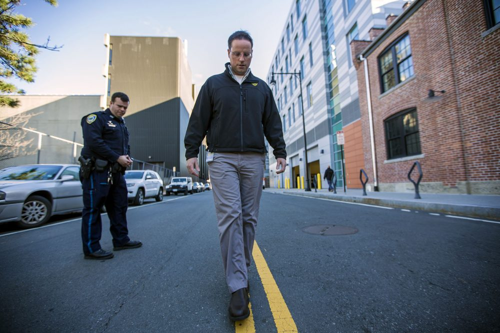 The state says it will work to increase the number of officers trained in specific programs to detect drug impairment in drivers, like Cambridge police officer Jason Callinan, a drug recognition expert, or DRE. Here, Callinan, left, and Jeremy Warnick, a spokesman for the department, demonstrate the walk and turn line test down the center of Rogers Street last year. (Jesse Costa/WBUR)