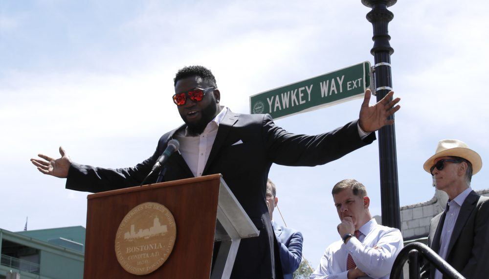 In this June 22, 2017 file photo, retired Boston Red Sox designated hitter David Ortiz is honored with the renaming of a portion of Yawkey Way to David Ortiz Drive outside Fenway Park in Boston. Red Sox principal owner John Henry, at right, says he wants to take steps to rename all of Yawkey Way, a street that has been an enduring reminder of the franchise's complicated racial past. At center rear is Boston Mayor Marty Walsh. (Charles Krupa/AP)
