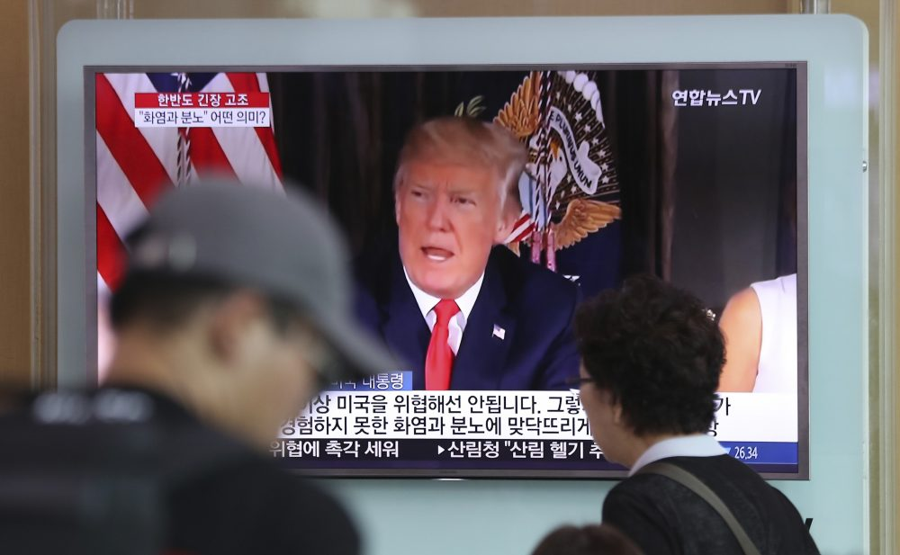 """People walk by a TV screen showing a local news program reporting with an image of U.S. President Donald Trump at the Seoul Train Station in Seoul, South Korea, Wednesday, Aug. 9, 2017. North Korea and the United States traded escalating threats, with President Donald Trump threatening Pyongyang """"with fire and fury like the world has never seen"""" and the North's military claiming Wednesday it was examining its plans for attacking Guam. (Lee Jin-man/AP)"""