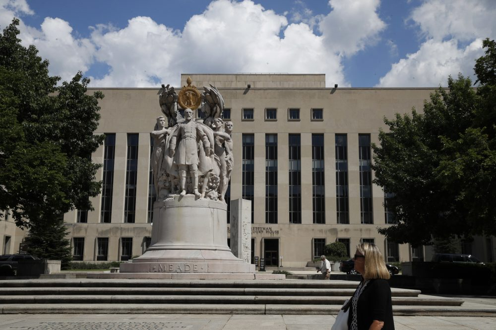 A woman walks past the George Gordon Meade Memorial in front of the E. Barrett Prettyman Federal Courthouse, Aug. 10, 2017, in Washington, where the Trump grand jury will meet. (Jacquelyn Martin/AP)
