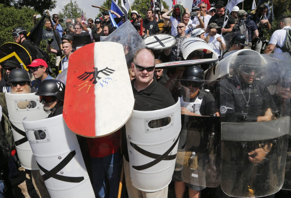 White nationalist demonstrators use shields as they guard the entrance to Lee Park in Charlottesville, Va., Saturday, Aug. 12, 2017. (Steve Helber/AP)