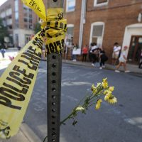 On Sunday, Aug. 13, 2017, police tape and flowers mark the site where a car plowed into a crowd of people protesting a white nationalist rally on Saturday in Charlottesville, Va. (Steve Helber/AP)