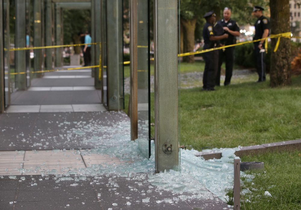 In this file photo, law enforcement officials stand near broken glass at the New England Holocaust Memorial in Boston in August 2017. Gov. Charlie Baker has announced the revival of a hate crime task force after a report showed an increase in hate crimes from 2016 to 2017. (Steven Senne/File/AP)