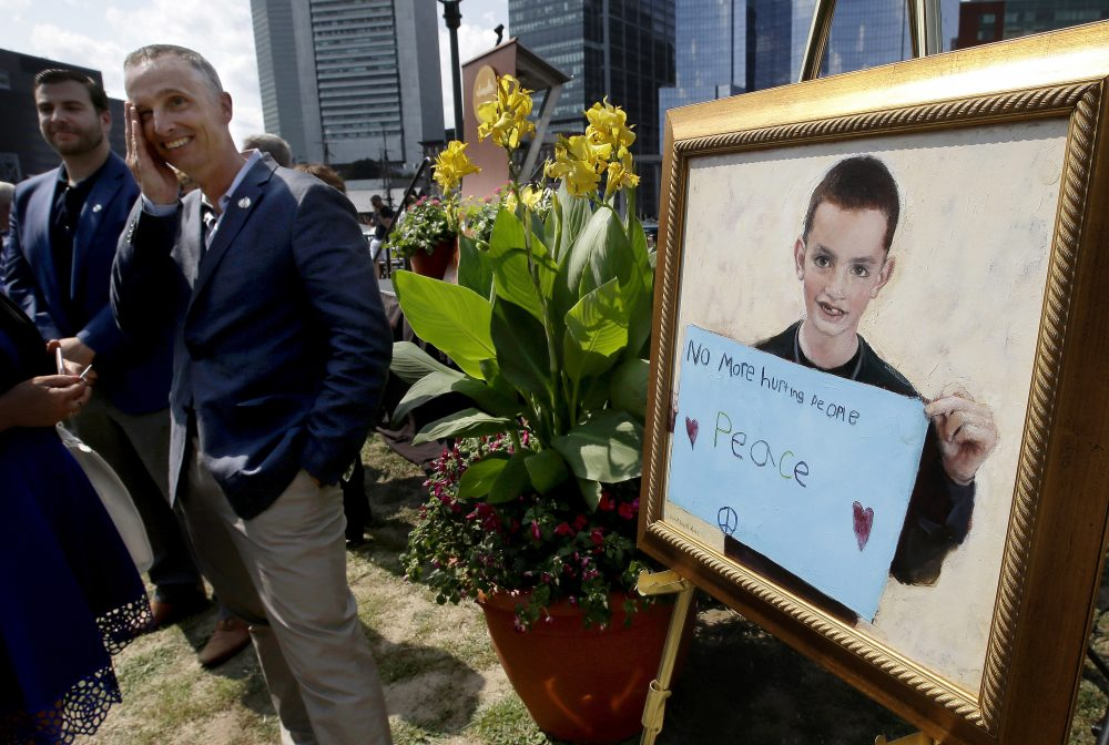 Bill Richard, father of Boston Marathon bombing victim Martin Richard, brings his hand to his face while standing next to a painting of Martin at the conclusion of groundbreaking ceremonies for a park named after his late son, Wednesday in Boston. (Steven Senne/AP)