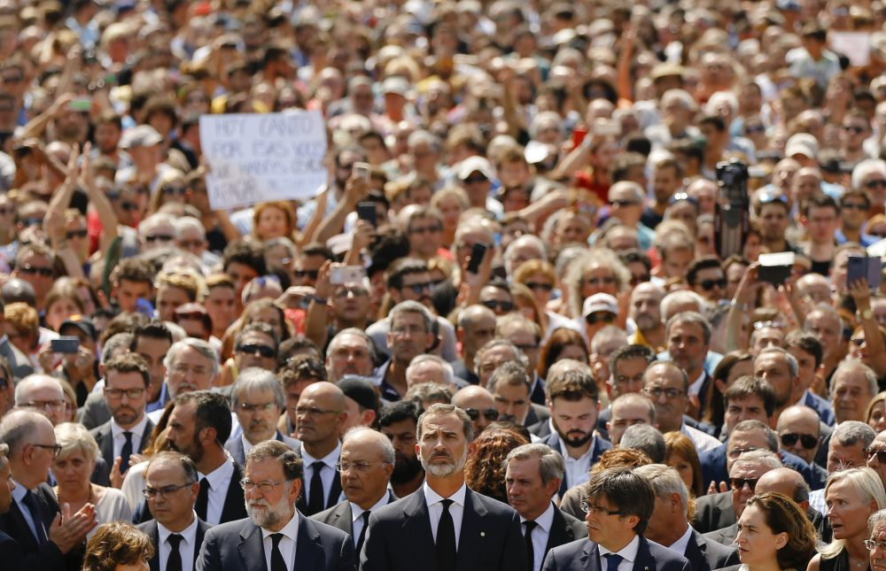King Felipe of Spain, center, Prime Minister Mariano Rajoy, center left, and and Catalonia regional President Carles Puigdemont, center right, join people observing a minute of silence in memory of the terrorist attacks victims Friday. (Francisco Seco/AP)