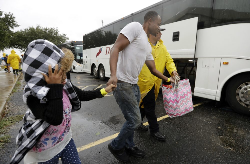 A family is helped to a bus as they are evacuated as the outer bands of Hurricane Harvey begin to make landfall, Friday, Aug. 25, 2017, in Corpus Christi, Texas. Harvey intensified into a hurricane Thursday and steered for the Texas coast with the potential for up to 3 feet of rain, 125 mph winds and 12-foot storm surges in what could be the fiercest hurricane to hit the United States in almost a dozen years.(AP Photo/Eric Gay)