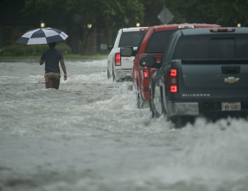 A pedestrian crosses a street inundated by floodwaters from Tropical Storm Harvey on Sunday, Aug. 27, 2017, in Houston, Texas. (Charlie Riedel/AP)
