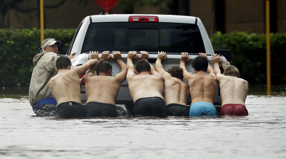 People push a stalled pickup through a flooded street in Houston, after Tropical Storm Harvey dumped heavy rains, Sunday, Aug. 27, 2017. The remnants of Harvey sent devastating floods pouring into Houston on Sunday as rising water chased thousands of people to rooftops or higher ground. (Charlie Riedel/ AP)