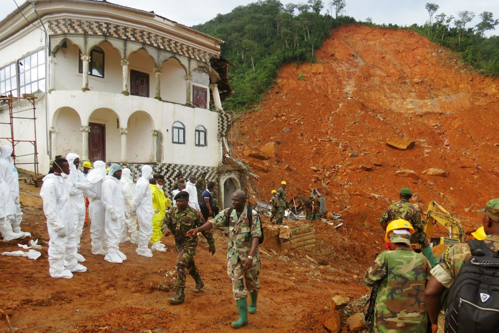 Search and rescue team members and soldiers operate near a mudslide site and damaged building near Freetown on Aug. 15, 2017, after landslides struck the capital of the west African state of Sierra Leone. (Mohamed Saidu BAH/AFP/Getty Images)