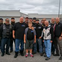 Phil Mick, center, with Brent Warfield, fourth from left, and other bikers who came to escort him to school. (Courtesy of Brent Warfield)