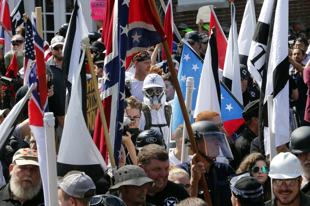 White nationalist demonstrators walk into the entrance of Lee Park surrounded by counter demonstrators in Charlottesville, Va., Saturday, Aug. 12, 2017. (Steve Helber/AP)