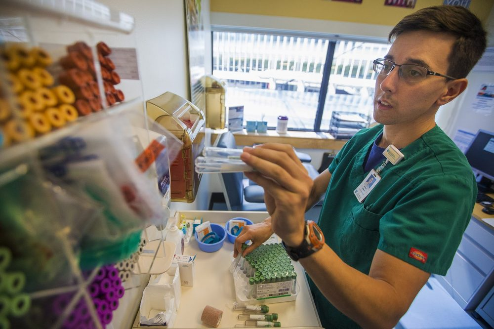 Jeff Osman restocks shelves with test tubes in the Biobank Phlebotomy Office at Massachusetts General Hospital. (Jesse Costa/WBUR)
