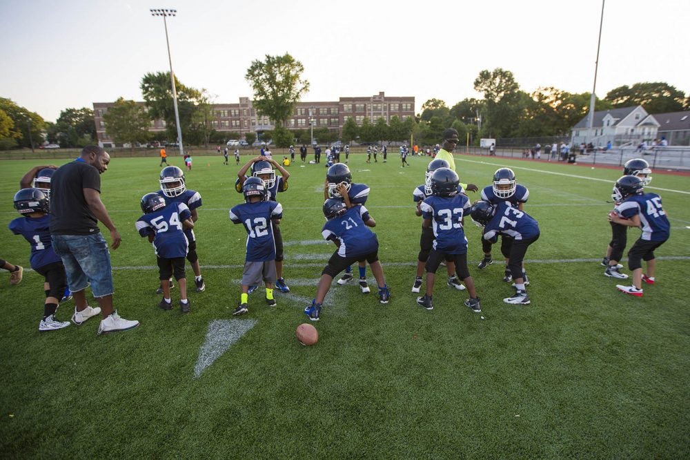 Youth football players of the Dorchester Eagles perform drills during practice in August 2016. (Jesse Costa/WBUR)
