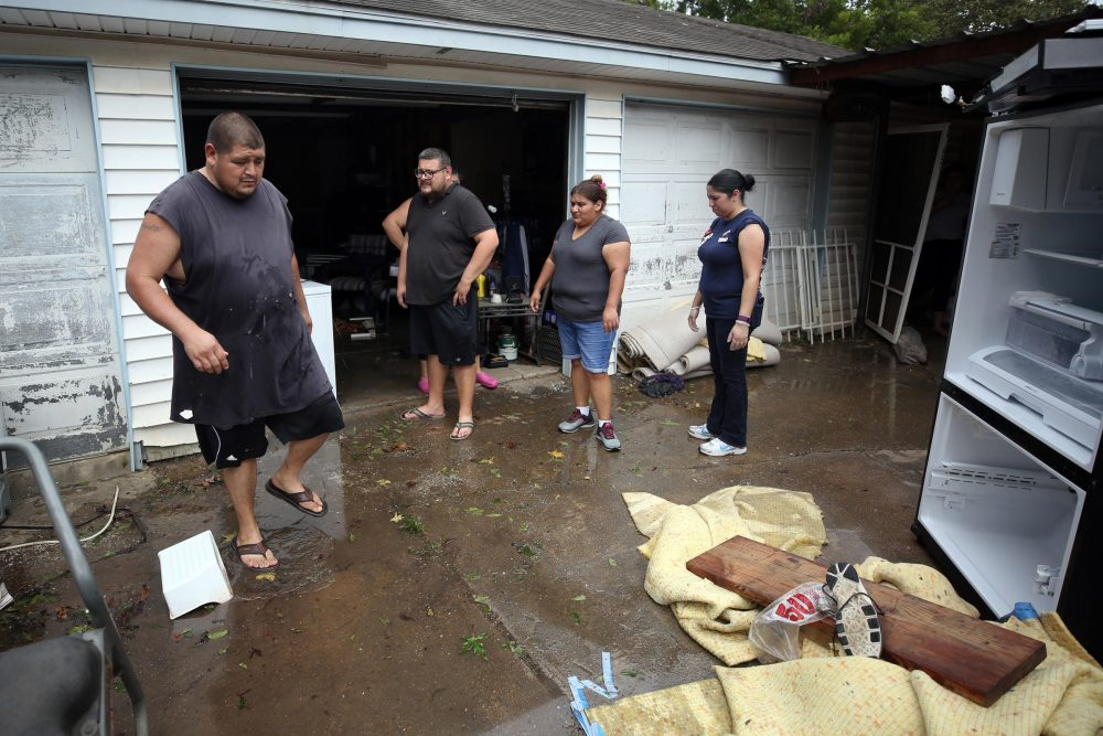 Garcia family members clean out their house and garage Wednesday in East Houston after the floods. (Jorge Sanhueza-Lyon/KUT News)