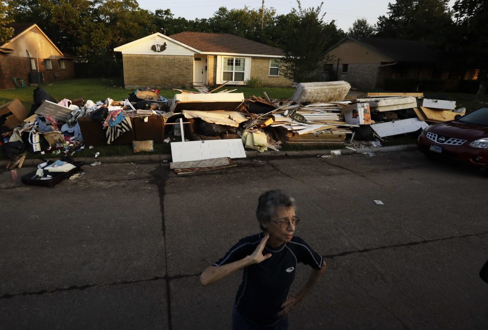 Joan Finmore looks out as she takes a break from sorting items at a friend's flooded home Saturday, Sept. 2, 2017, in Houston. Thousands of people have been displaced by torrential rains and catastrophic flooding since Harvey slammed into Southeast Texas last Friday. (AP Photo/Gregory Bull)