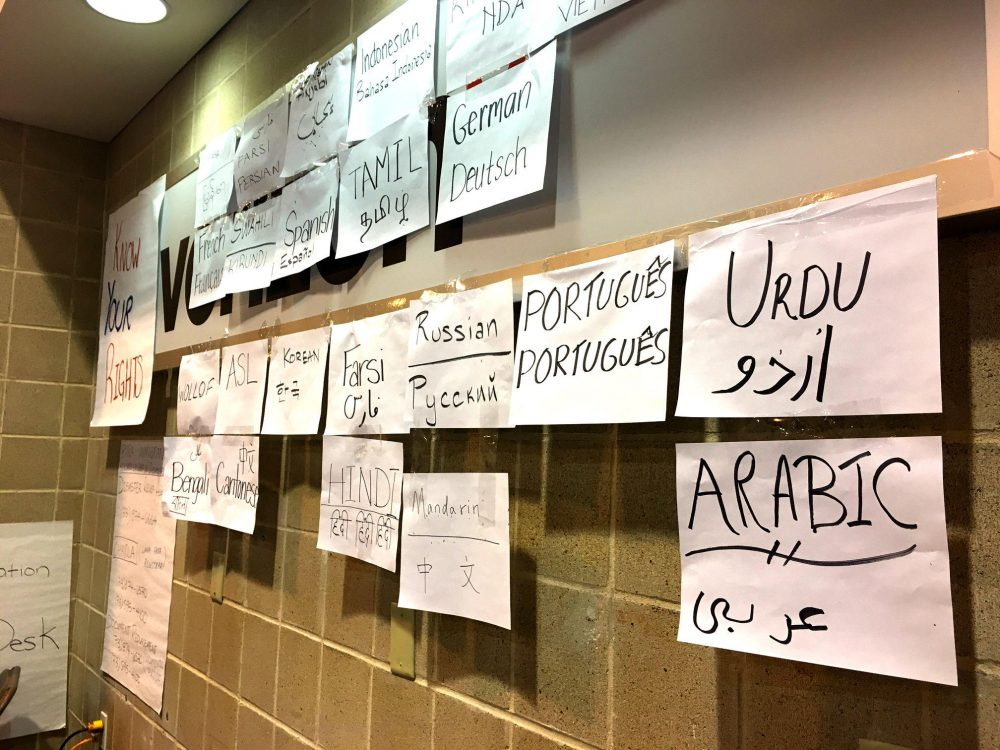 Houston Immigration Legal Services Collaborative is set up at the NRG Center, with several posters that hope to welcome undocumented immigrants and encourage them to get help. (Stella M. Chavez/KERA News)