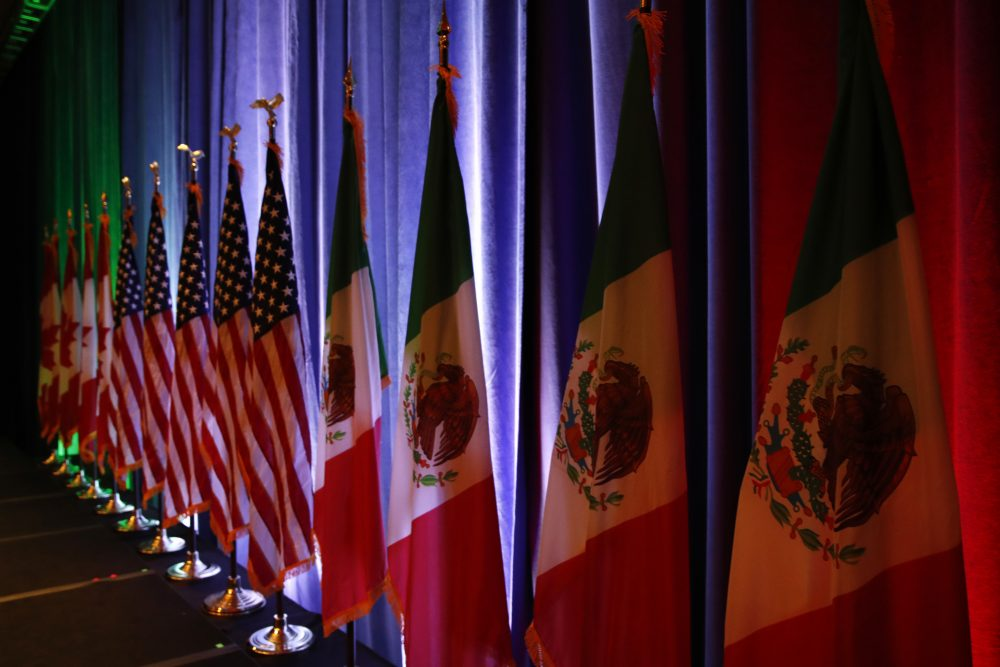 The national flags of Canada, the U.S. and Mexico are lit by stage lights before a news conference, at the start of the North American Free Trade Agreement renegotiations in Washington on Aug. 16, 2017. (Jacquelyn Martin/AP)