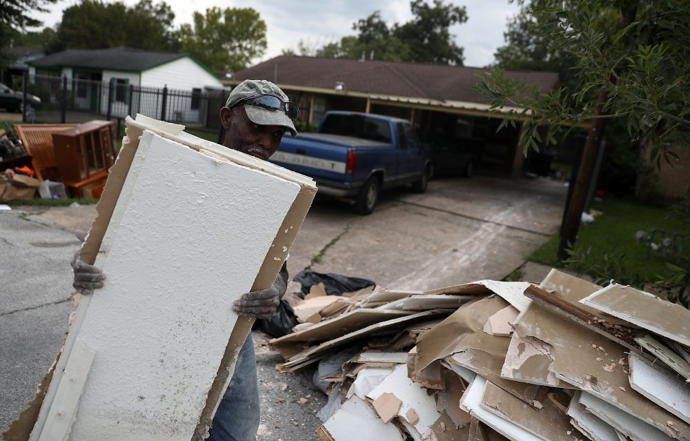 Rufus Lee of Top to Bottom Home Renovations carries moldy drywall out of a flood damaged home that he is cleaning out on Sept. 5, 2017, in Houston. (Justin Sullivan/Getty Images)
