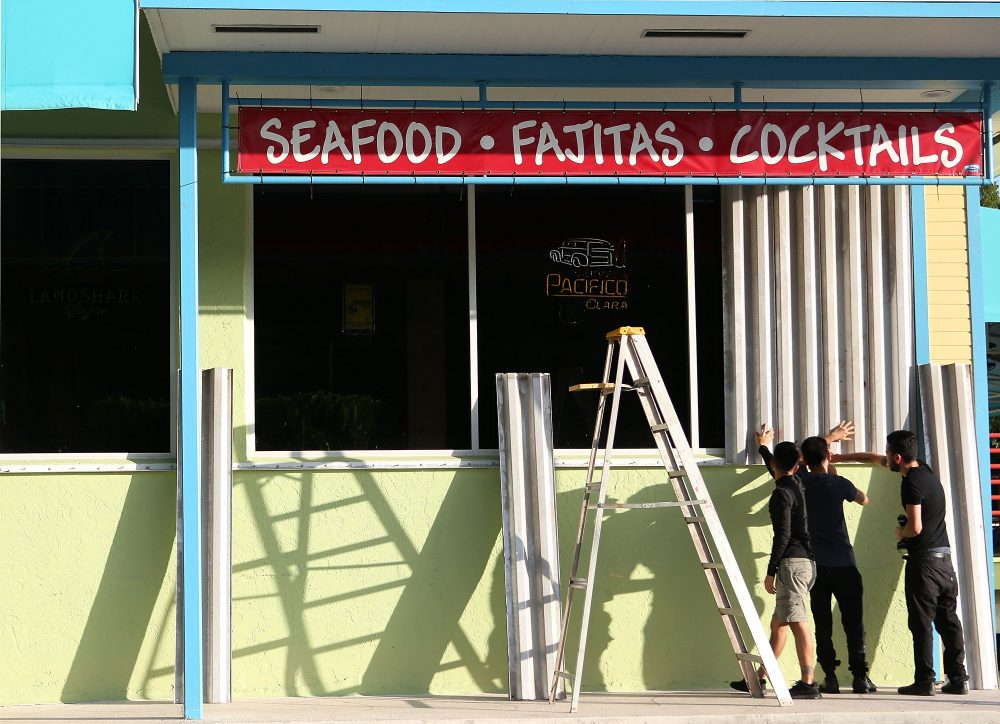 Workers install hurricane shutters on the Puerto Villarta restuarant on Overseas Highway in the Florida Keys on Sept. 5, 2017 in Islamorada, Fla. Residents are evacuating ahead of Hurricane Irma, a powerful storm expected to make landfall this weekend. (Marc Serota/Getty Images)