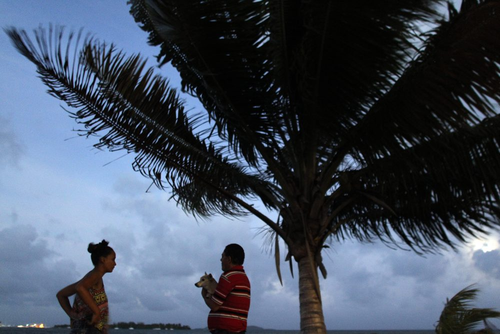A couple watch the sunset from a seafront as Hurricane Irma approaches Puerto Rico in Fajardo on Sept. 5, 2017. (Ricardo Arduengo/AFP/Getty Images)