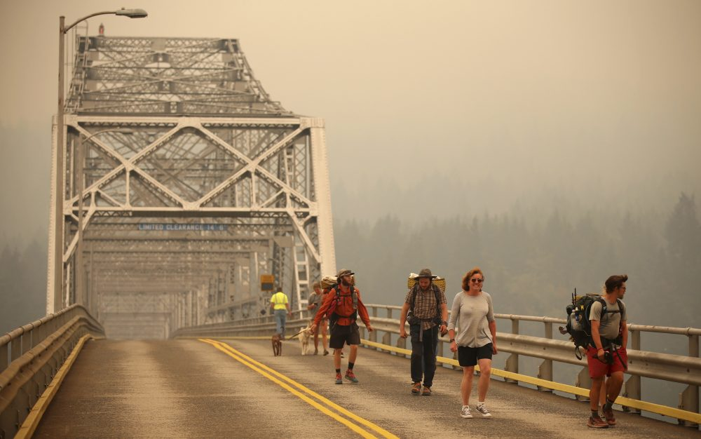 Pedestrians walk off the Bridge of the Gods, which spans the Columbia River between Washington and Oregon states, as smoke from the Eagle Creek wildfire obscures the Oregon hills in the background near Stevenson, Wash., Wednesday, Sept. 6, 2017. (Randy L. Rasmussen/AP)