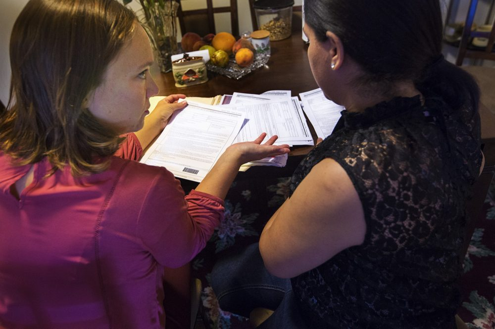 Some immigrants living here without authorization who've been victims of crime in the U.S. may be eligible for a U visa. The application process and lengthy wait time used to be a deterrent, but that appears to be changing under the Trump administration. Here, immigration lawyer Susan Roses, left, reviews documents and with Antonia concerning her U-visa filing. (Jesse Costa/WBUR)