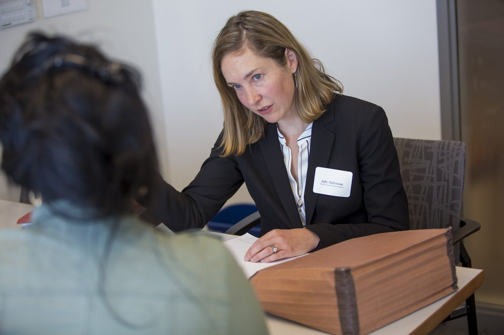 Julie Dahlstrom, director of Boston University's Immigrants' Rights & Human Trafficking Program, consults with a client who is awaiting an answer about the U visa she applied for two years ago. (Jesse Costa/WBUR)