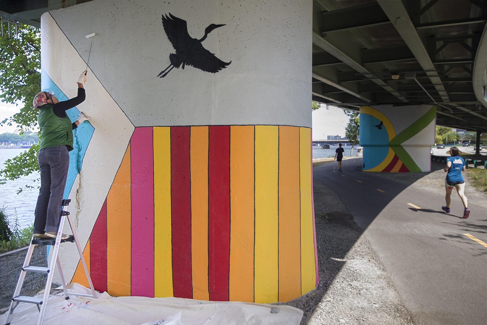 Artist Silvia López  Chavez applies an anti-graffiti solution to her mural on the Esplanade's Dr. Paul Dudley White Bike Path. (Jesse Costa/WBUR)