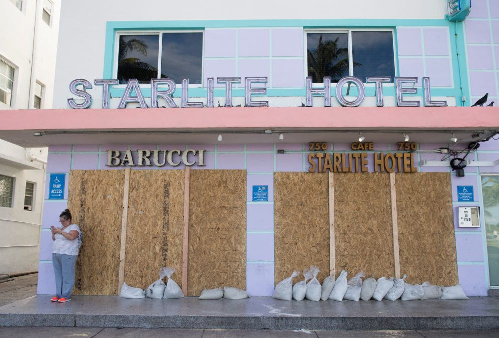 A woman uses her cellphone alongside a boarded-up hotel following mandatory evacuation orders in Miami Beach, Florida, Sept. 7, 2017, ahead of Hurricane Irma. (Saul Loeb/AFP/Getty Images)