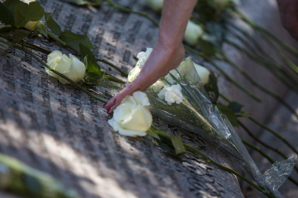 A visitor touches a name on the 9/11 Memorial in the Public Garden. (Jesse Costa/WBUR)