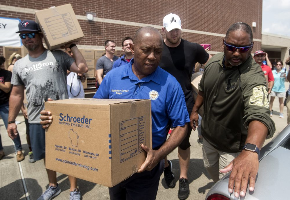 Houston Mayor Sylvester Turner, center, with Houston Texans Shane Lechler, left, and J.J. Watt, second right, distribute relief supplies to people impacted by Hurricane Harvey on Sept. 3 in Houston. (Brett Coomer/Houston Chronicle via AP, pool)