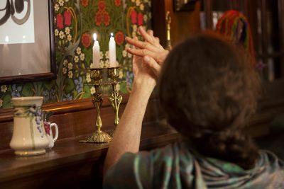 Susie recites a prayer after lighting the Shabbat candles to introduce the Jewish Sabbath. (Jesse Costa/WBUR)
