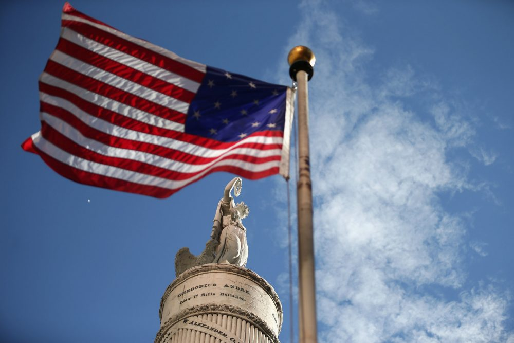 A U.S. flag with 15 stripes and 15 stars, like the one that was flown Fort McHenry during the War of 1812, frames the Battle Monument during the Star Spangled Spectacular Sept. 12, 2014, in Baltimore. (Chip Somodevilla/Getty Images)