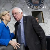 Sen. Elizabeth Warren speaks with Sen. Bernie Sanders at the Senate Health, Education, Labor, and Pensions Committee hearing with governors to discuses ways to stabilize health insurance markets. (Jose Luis Magana/AP)