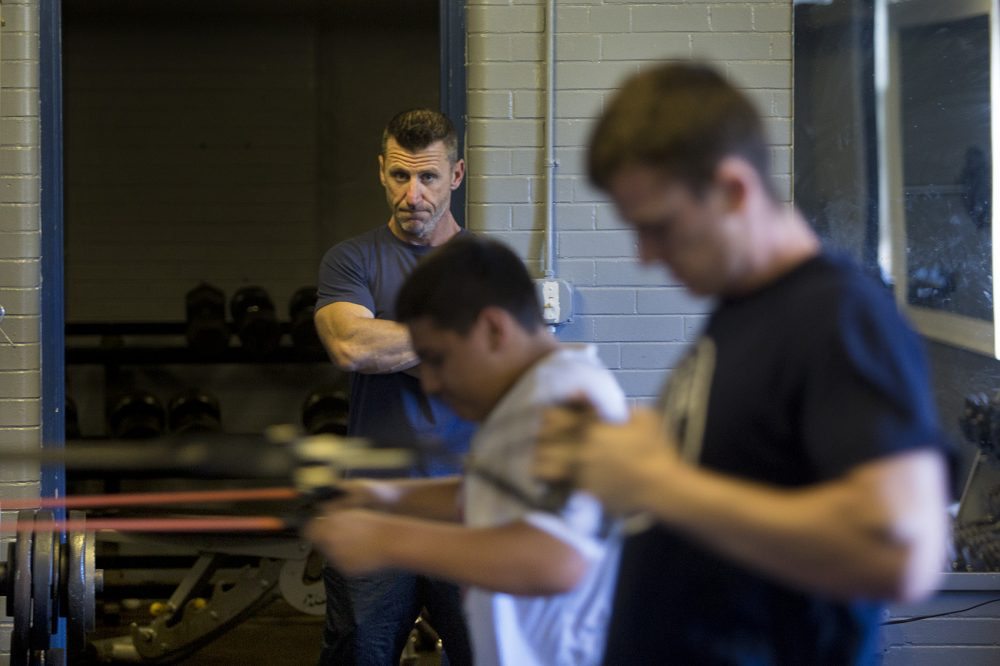 Marine veteran Jeff Buckley keeps an eye on workout participants doing band pulls in the basement of All Dorchester Sports and Leadership at Town Field. (Jesse Costa/WBUR)